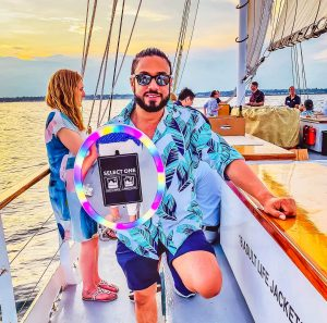 Picture of a man holding the MobileMax (a roaming photo booth) on a boat.