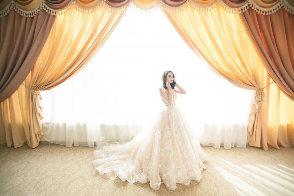 Bride standing in front of a window with lots of curtains.