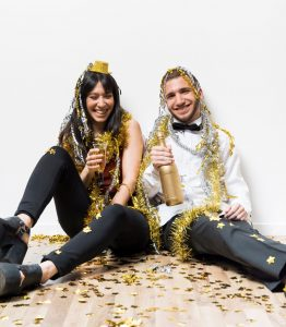 Couple sitting with golden garlands on them for new year