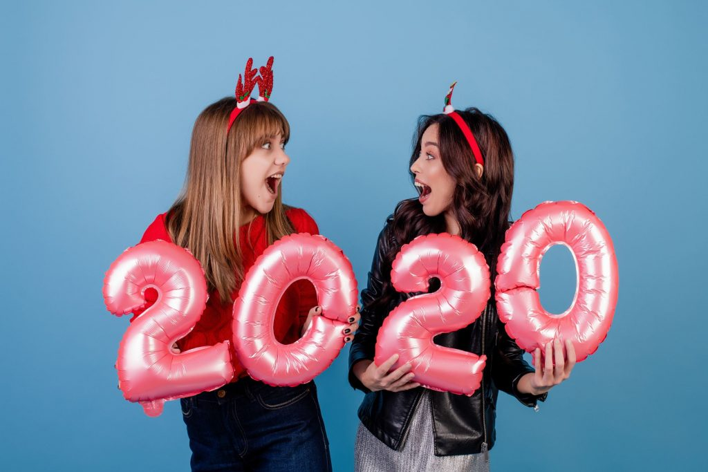 Women Taking picture with balloons for 2020 in a photo booth